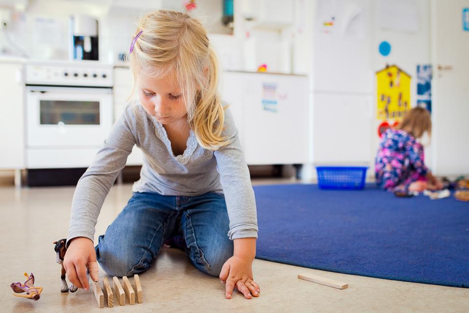 Ett barn leker med klossar på golvet på en förskola.
