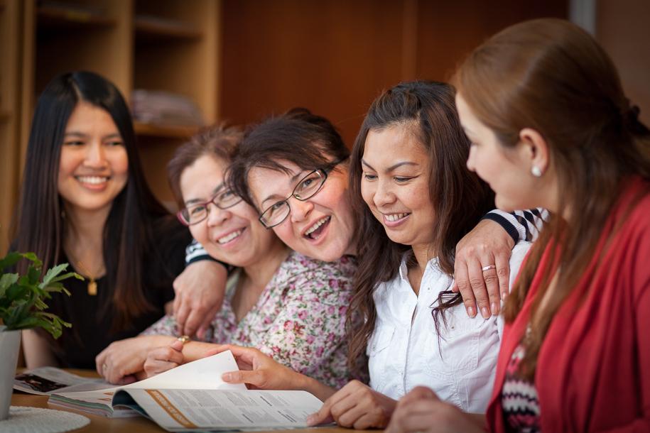 Glada elever sitter vid ett bord utanför Studiehallen.