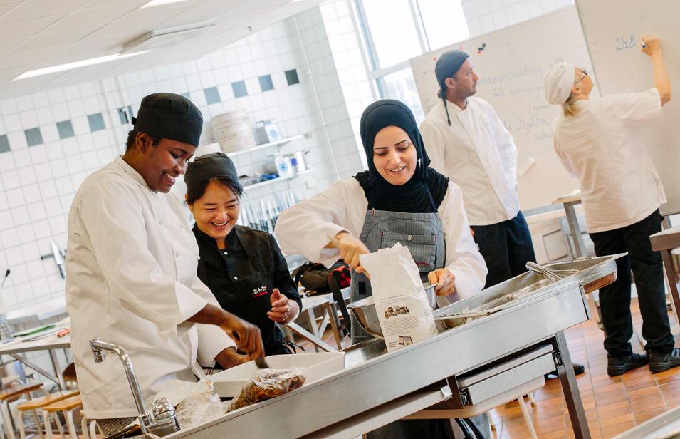 En grupp elever lagar mat i ett kök.