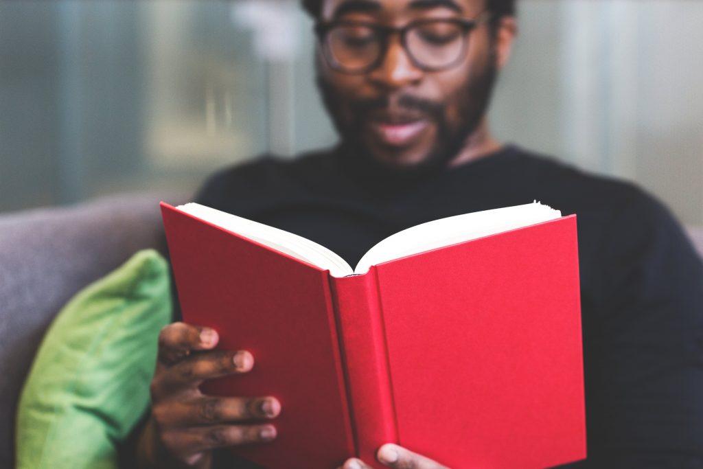 man läser röd bok