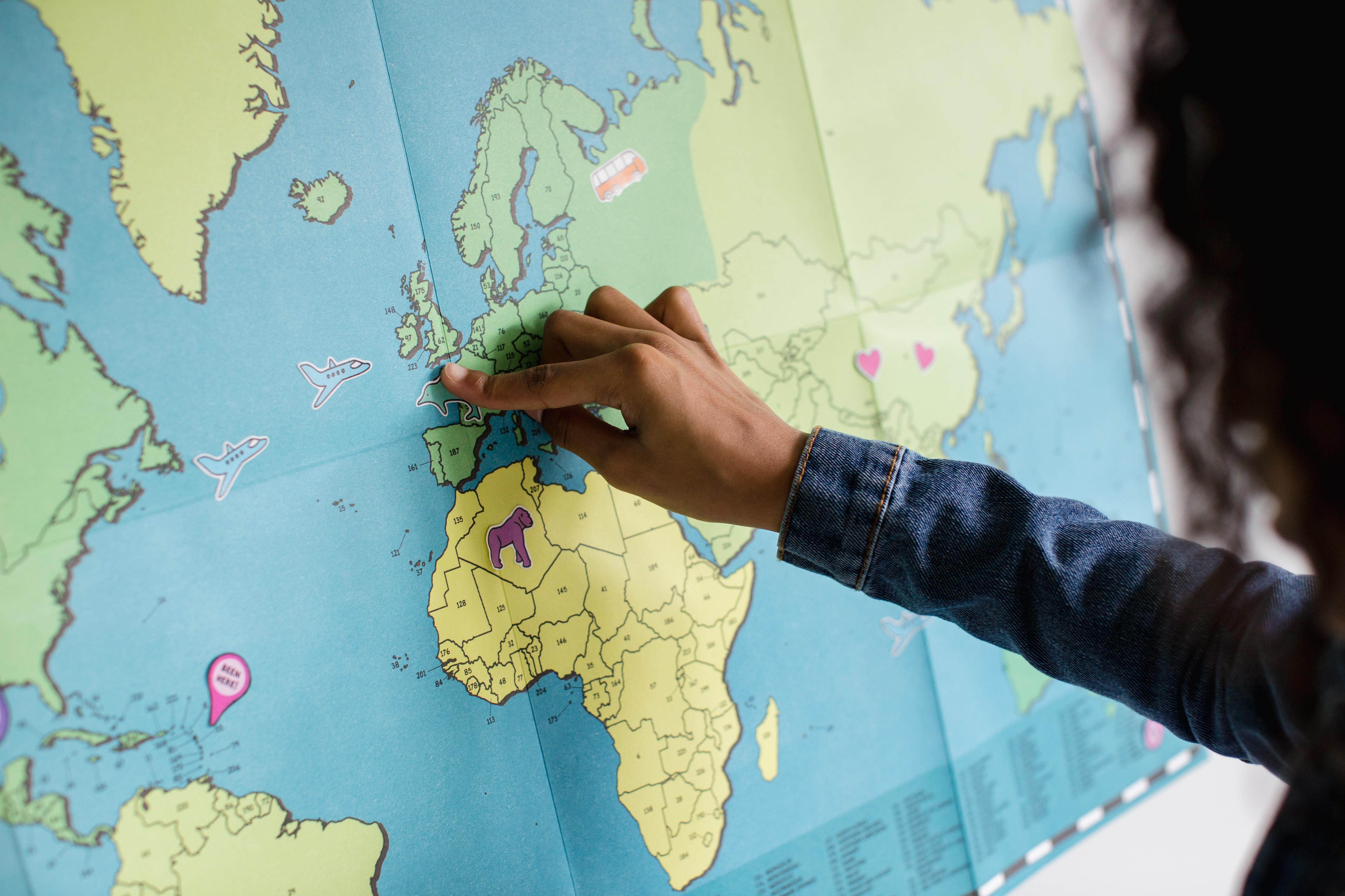 hand pekar på världskarta