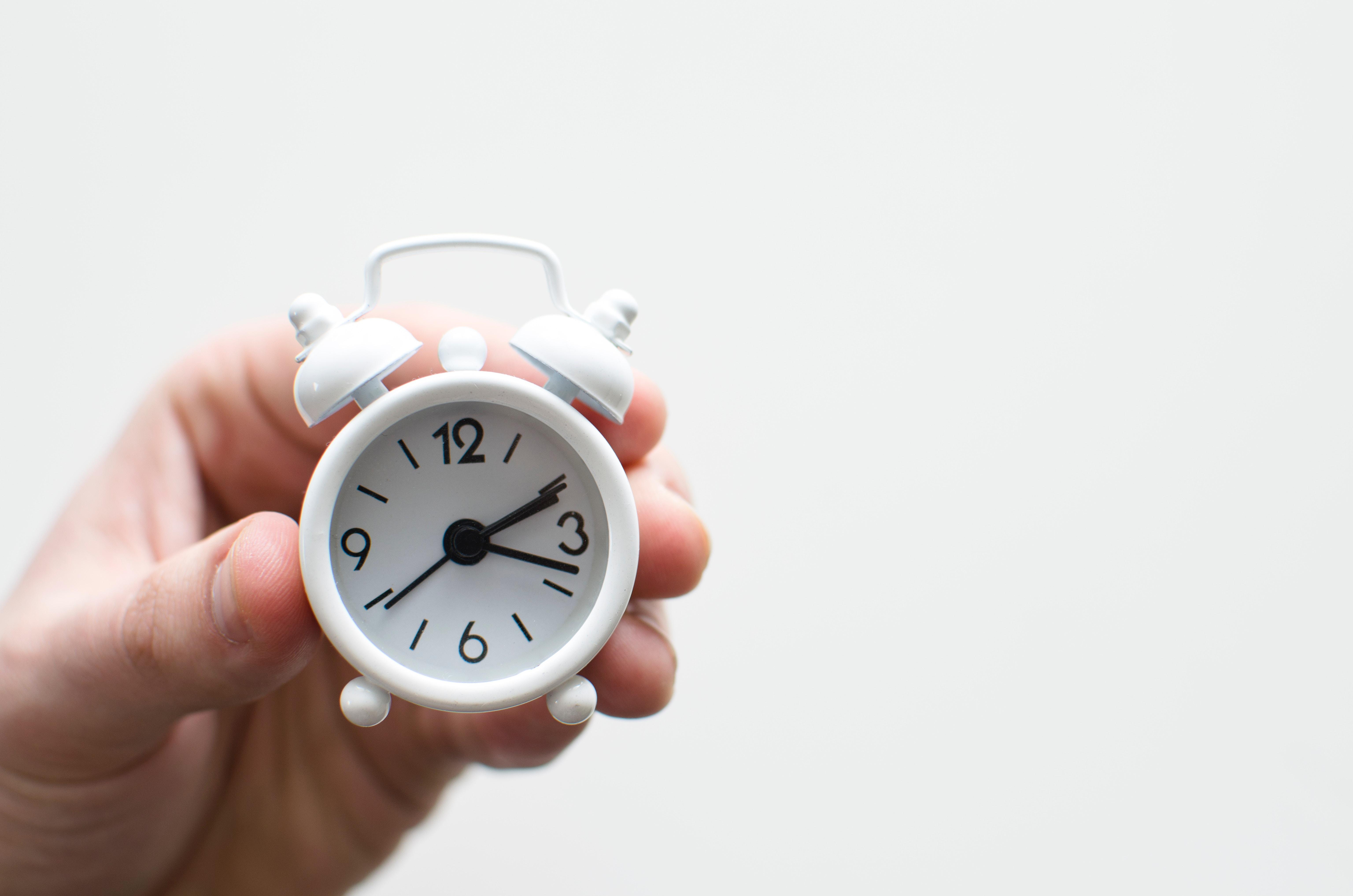 hand håller liten klocka