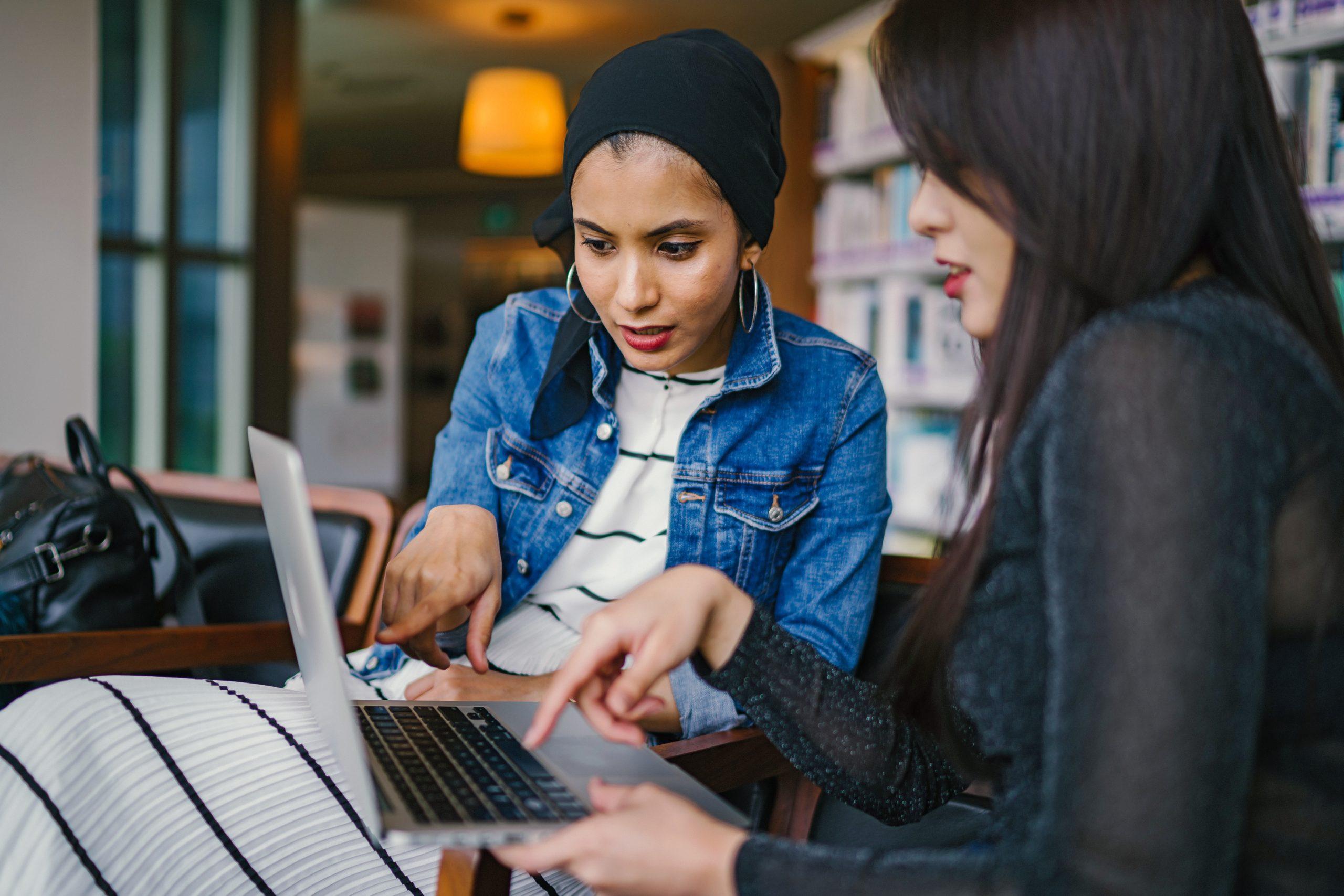 två kvinnor tittar och pekar på dator