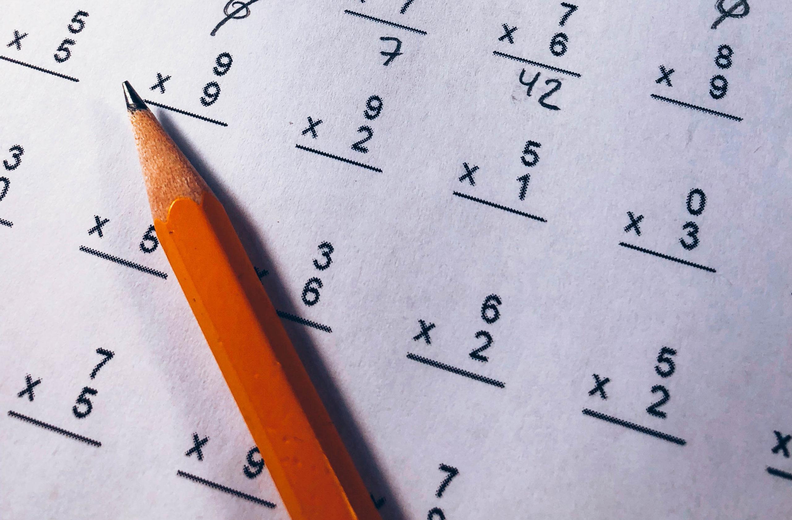 Räkneuppgifter på ett papper med en blyertspenna liggande ovanpå.
