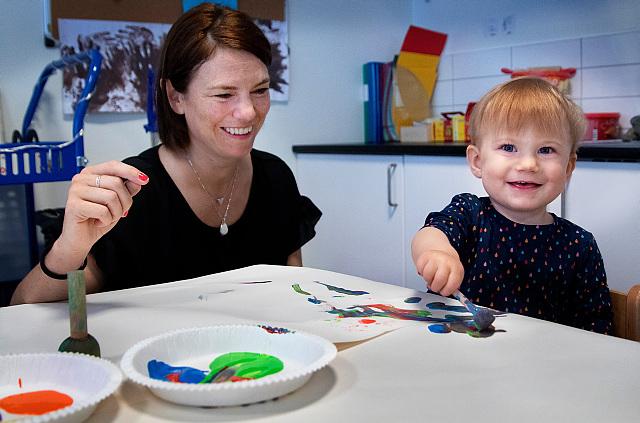 En vuxen sitter vid ett barn som målar.
