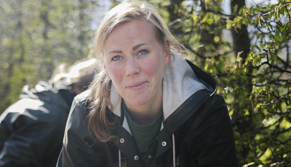 Kvinna med träd i bakgrunden tittar in i kameran och ler.
