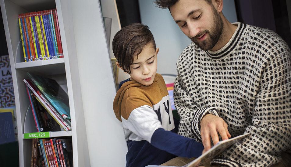 En man läser för en liten pojke.