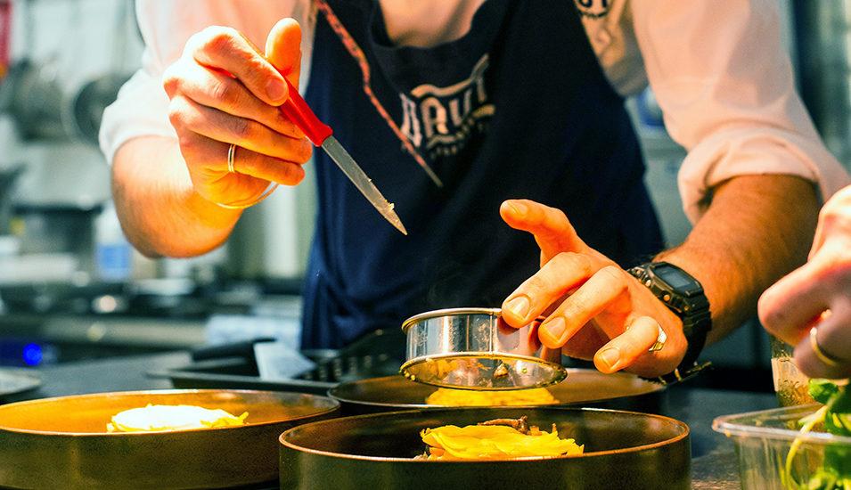 Närbild på händer som lägger upp mat på en tallrik.