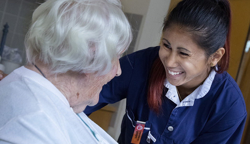 Yngre kvinna i arbetskläder lutar sig fram och ler mot äldre kvinna.