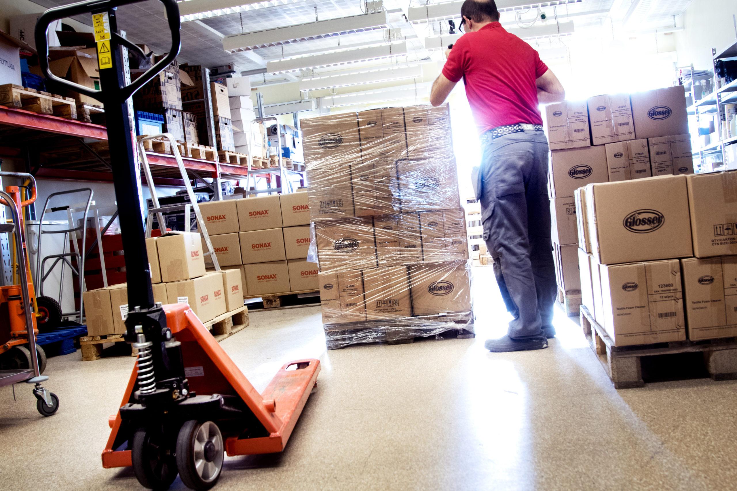 Person i arbetskläder står vid en pall med lådor på i lagermiljö.