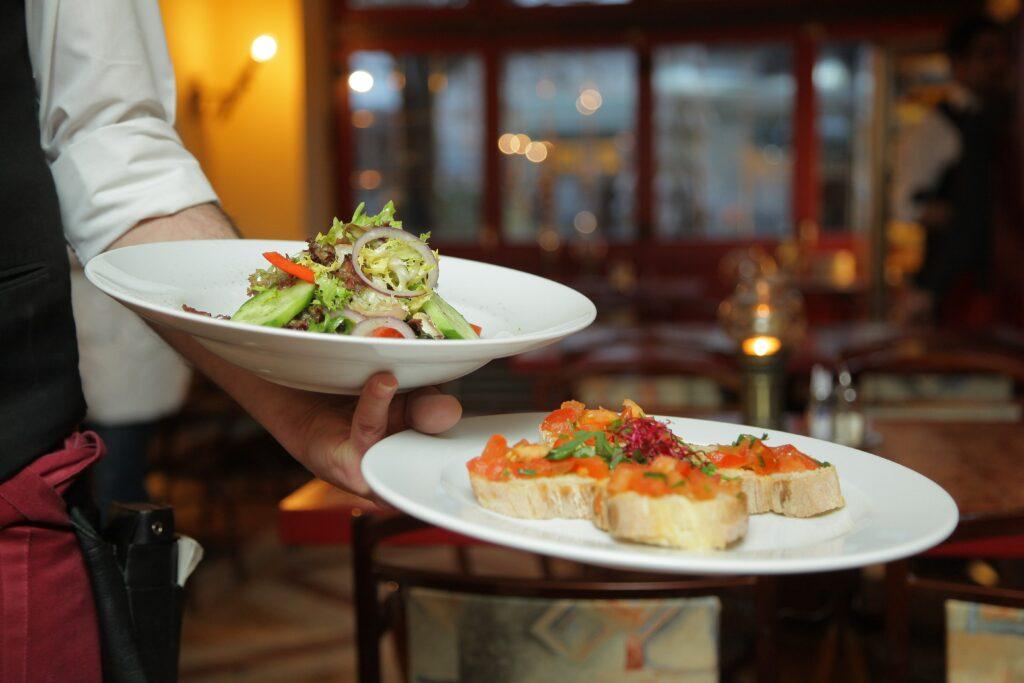 Två tallrikar med fint upplagd mat balanseras på en servitörs arm.