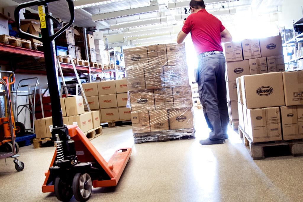 En person tar hand om en pall med varor på ett lager.