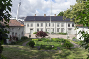 Landeriet, en gammal träbyggnad omgiven av grönska och med Ullevi i bakgrunden.